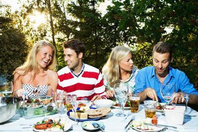 Fire unge personer spiser middag ute i hagen. Foto.