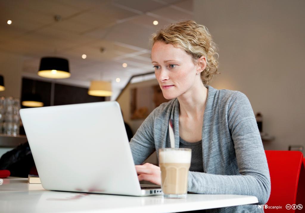 Kvinne sitter på en kafe med laptop. Foto.