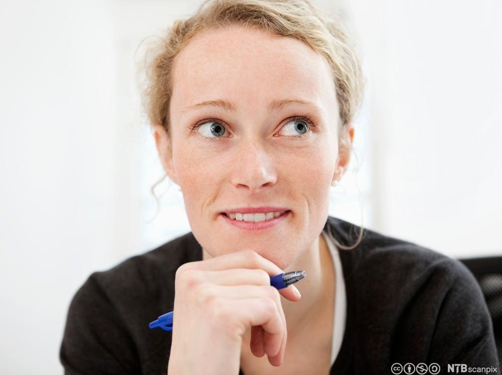 Kvinne sitter med hånden under haka og tenker. Foto.