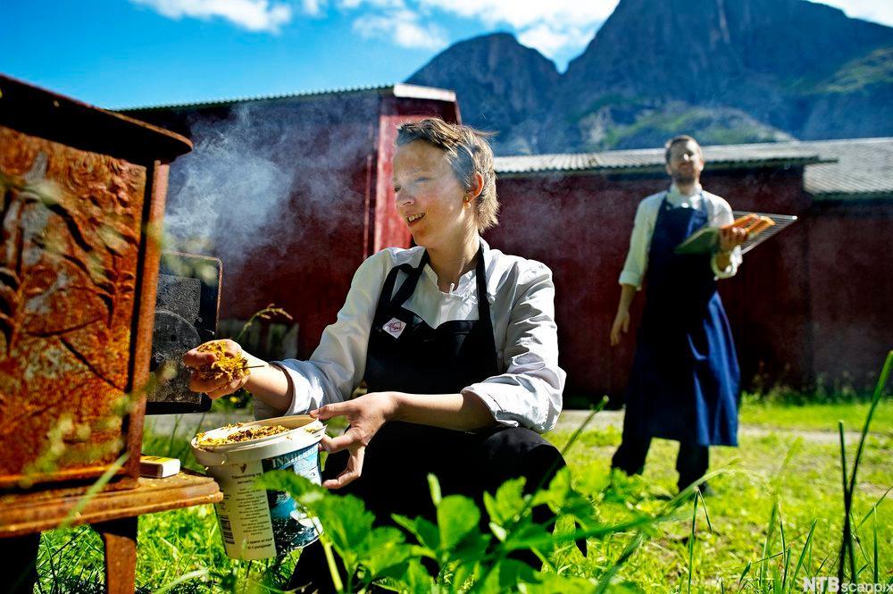 Bilde av en dame som putter mat i en hjemmelaget røykovn. Foto