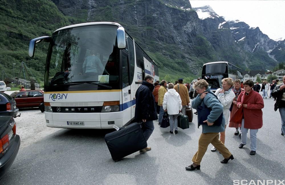 Turbuss med passasjerer utenfor. foto.