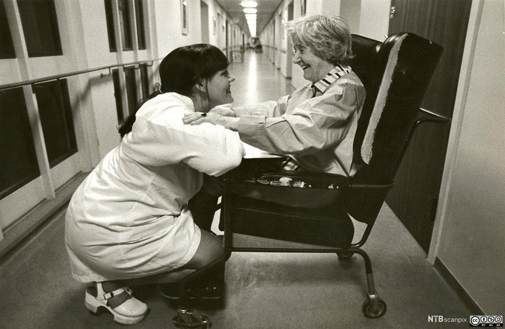 Pleier og pasient ser på hverandre og smiler. Foto