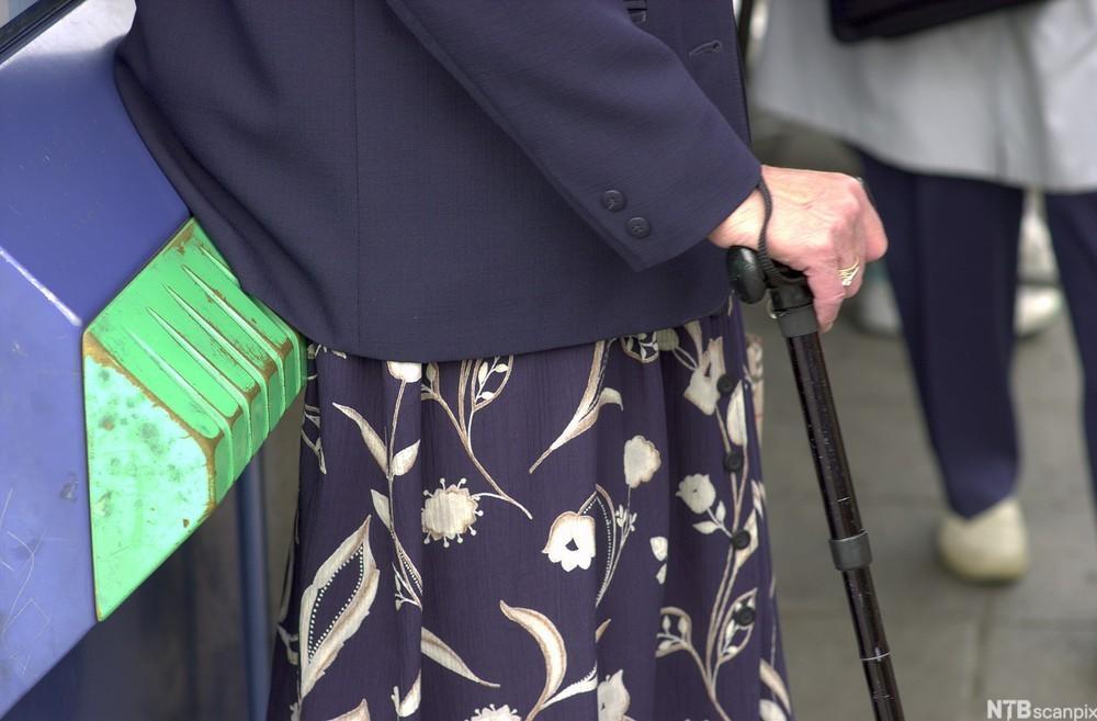 Eldre kvinne med stokk. foto.