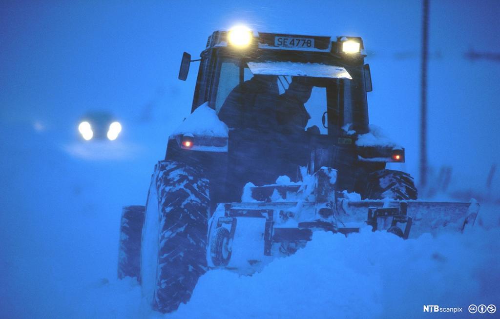 Traktor brøyter vei i mørket i snøstorm på Karmøy. Foto.