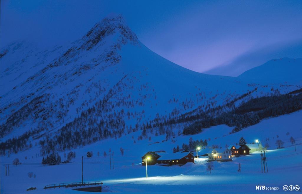 Oversiktsbilde over snødekt vinterlandskap. Fjelltopper i bakgrunnen og en større gård med opplyste vinduer lenger framme. Foto.