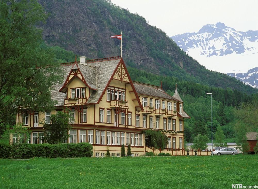 Hotell med fjell i bakgrunn. Foto.