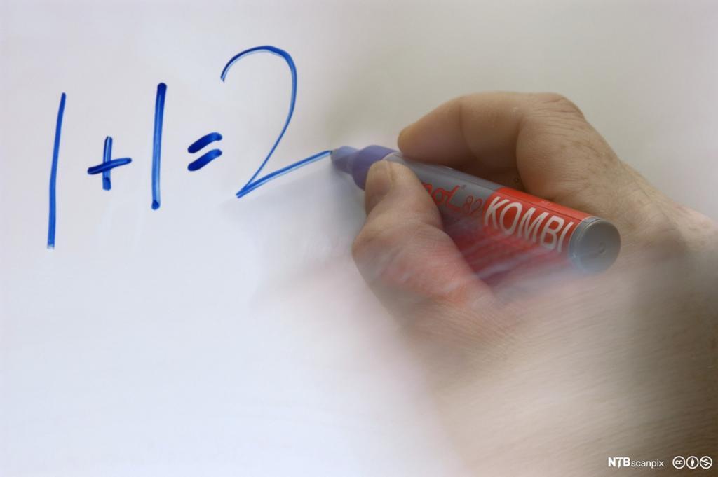 Hånd som skriver et regnestykke på tavla. Foto.