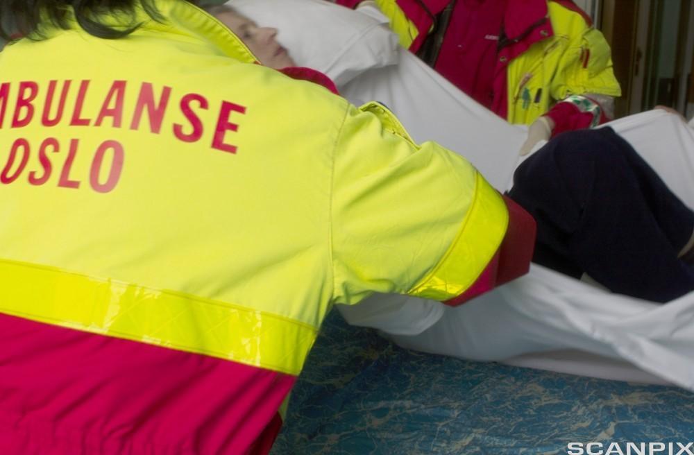Pasient forflyttes av ambulansesjåfører.Foto.