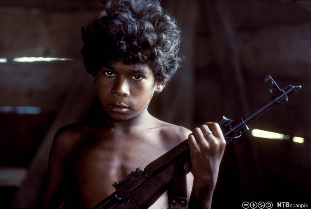 Liten gutt med automatvåpen. Foto.