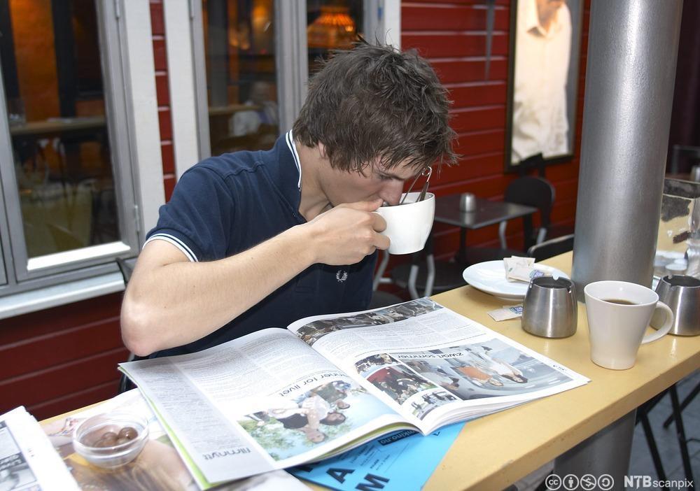 Ung gutt leser avis på kafe. Foto.