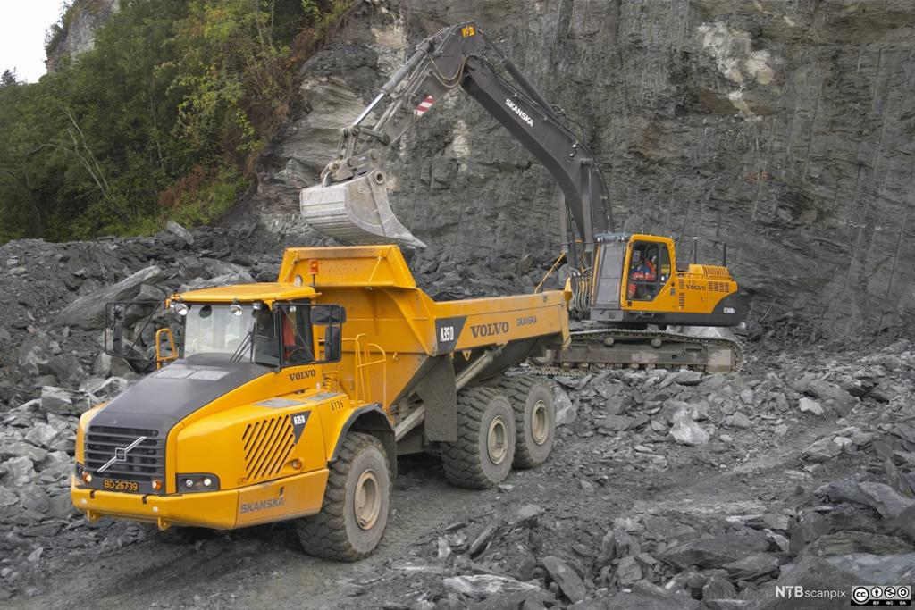 Dumper og gravemaskin i steinbrudd. Foto.