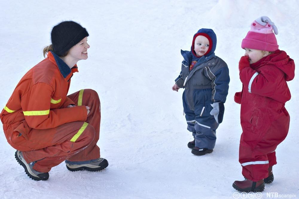 Barnehageansatt prater med to barn. Foto.