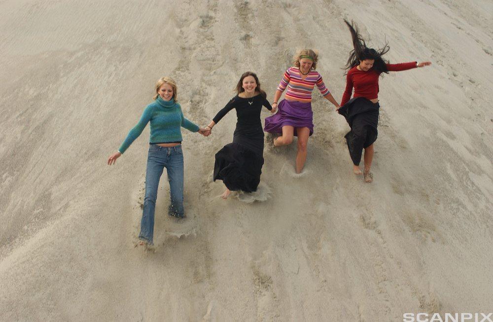 Fire unge kvinner løper hånd i hånd. Foto.