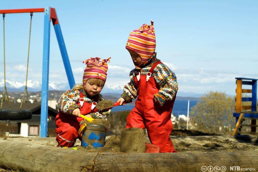 To små barn leker i sandkasse. Foto.