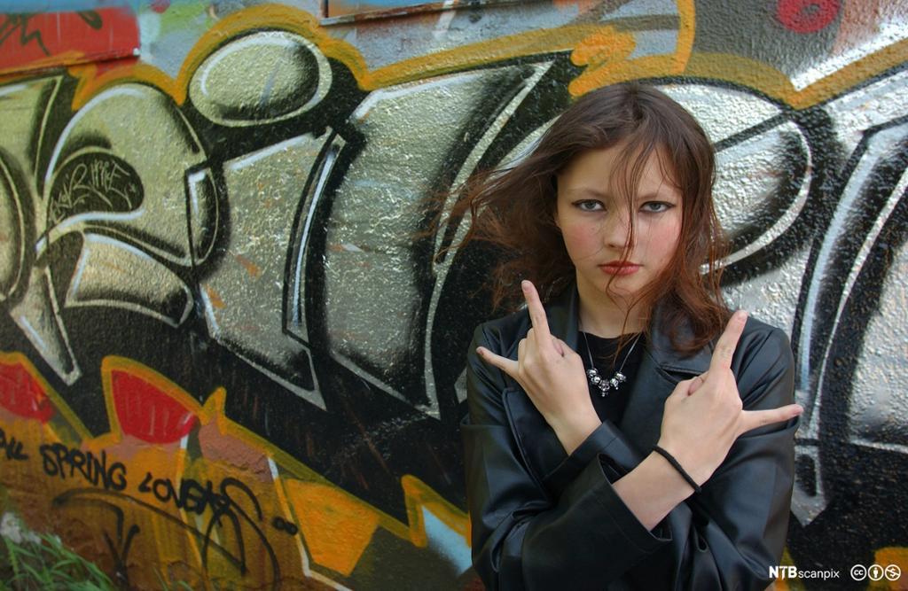 Ung jente som foran graffittivegg. Foto
