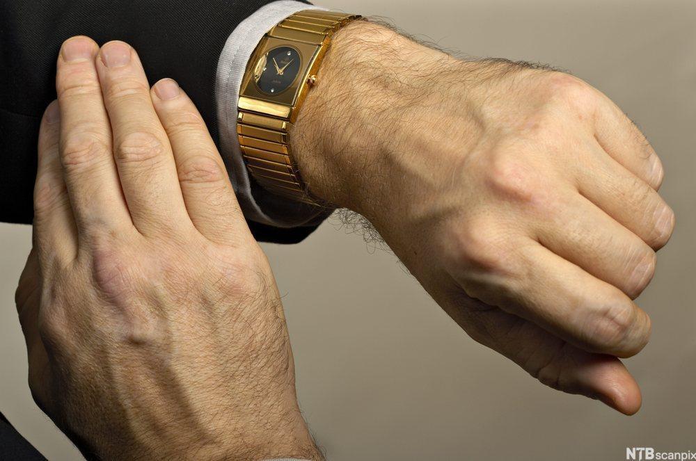 Mann ser på klokken. Foto.