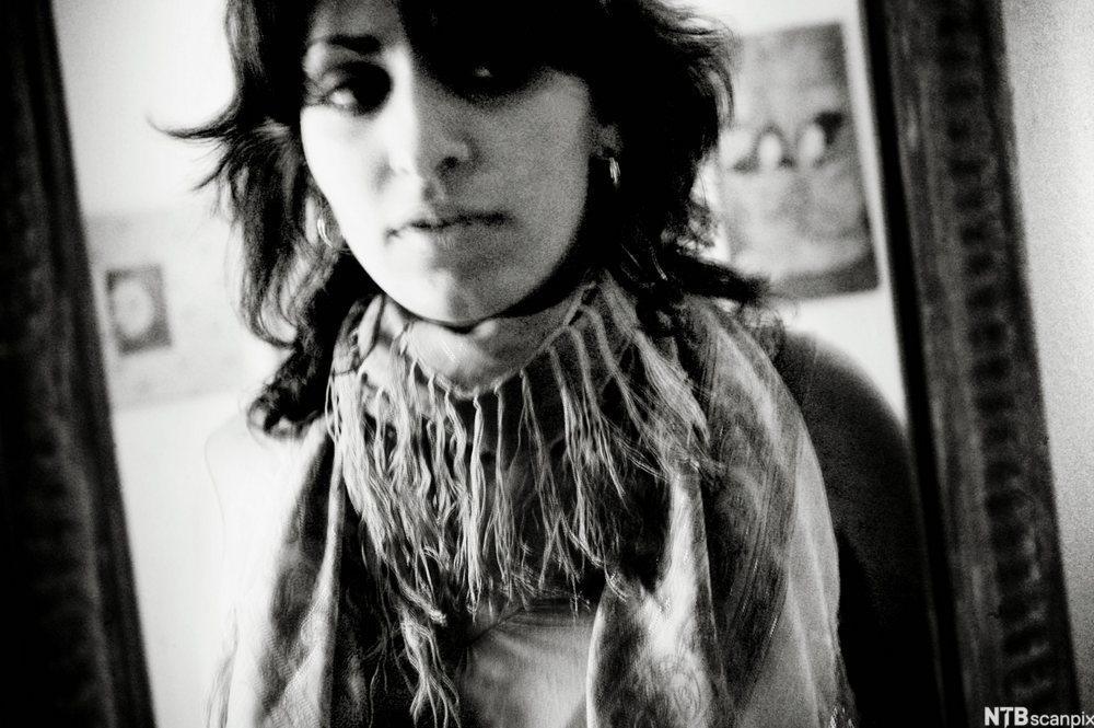 Portrett av ung kvinne i ein spegel. Foto.
