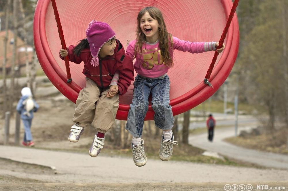 To glade jenter på en stor huske. Foto,