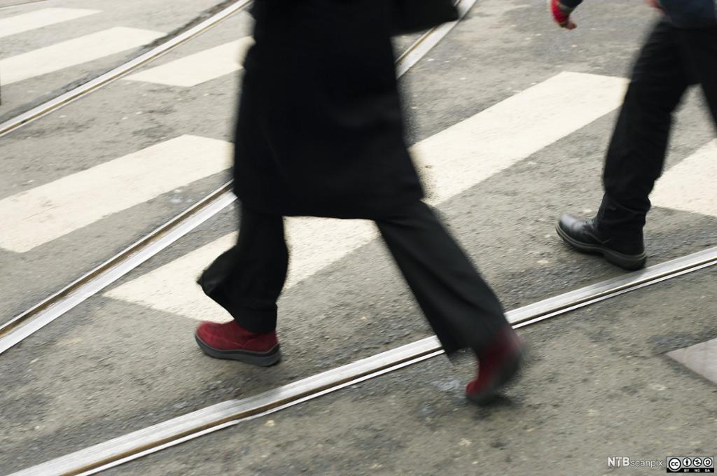 Personer krysser trikkespor. Foto.