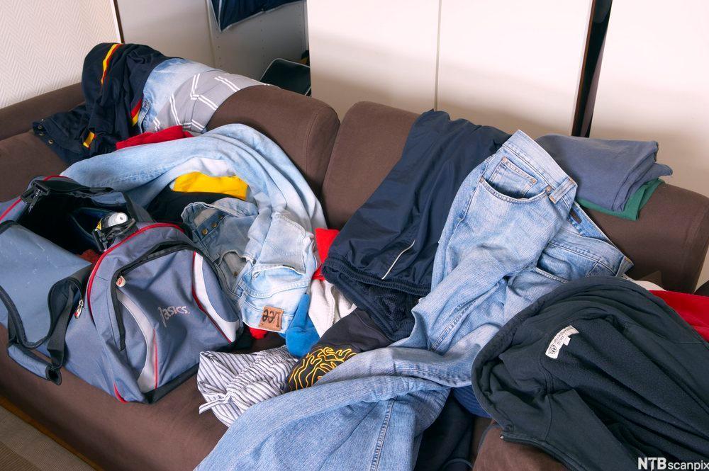 Rotete rom med klær hulter til bulter på en sofa. Foto.