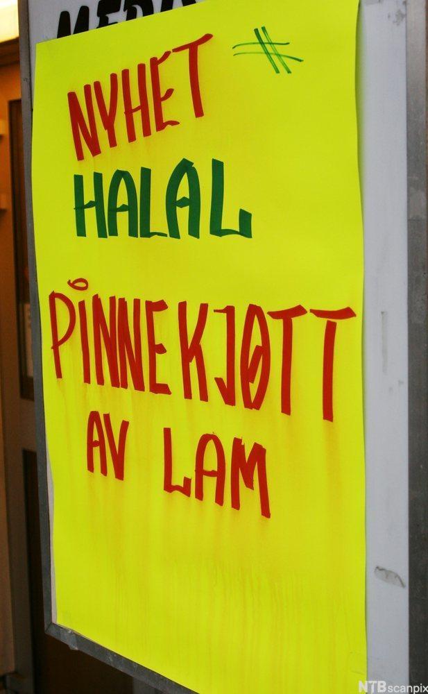 Plakat utenfor butikk. Selger halal pinnekjøtt av lam. Foto.