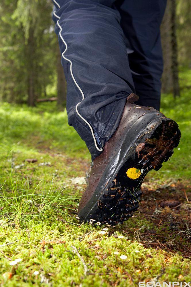 En person går med fjellstøvler i skogen. Foto.