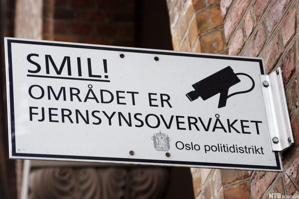 Skilt med tekst Smil! Området er fjernsynsovervåket. Oslo Politidistrikt. Foto.