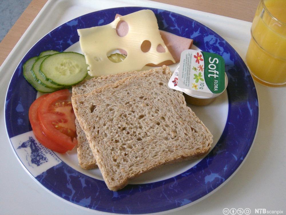 Glass med juice og asjett med to brødskiver, ost, skinke, tomat, agurk og smør på et brett. Foto.