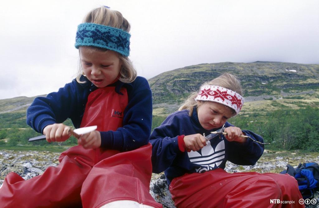To jenter bruker kniv og spikker på en pinne. Foto.
