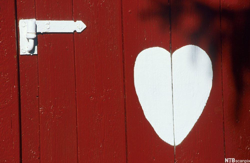 Hvitmalt hjerte på rødmalt dør. foto.