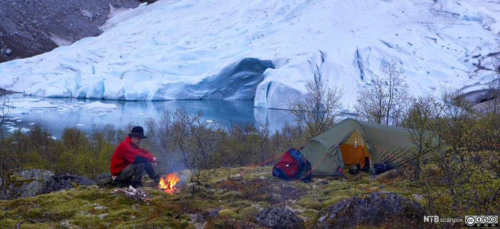 Fjellvandrer tenner bål ved Briksdalsbreen. Foto.