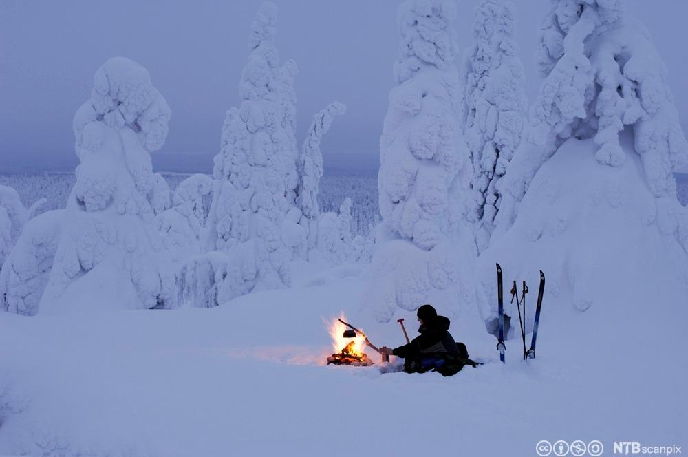 Person sitter ved bål i vinterlandskap. Foto.