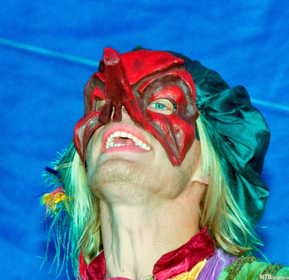 Leende mann med fargerik maske. Foto.