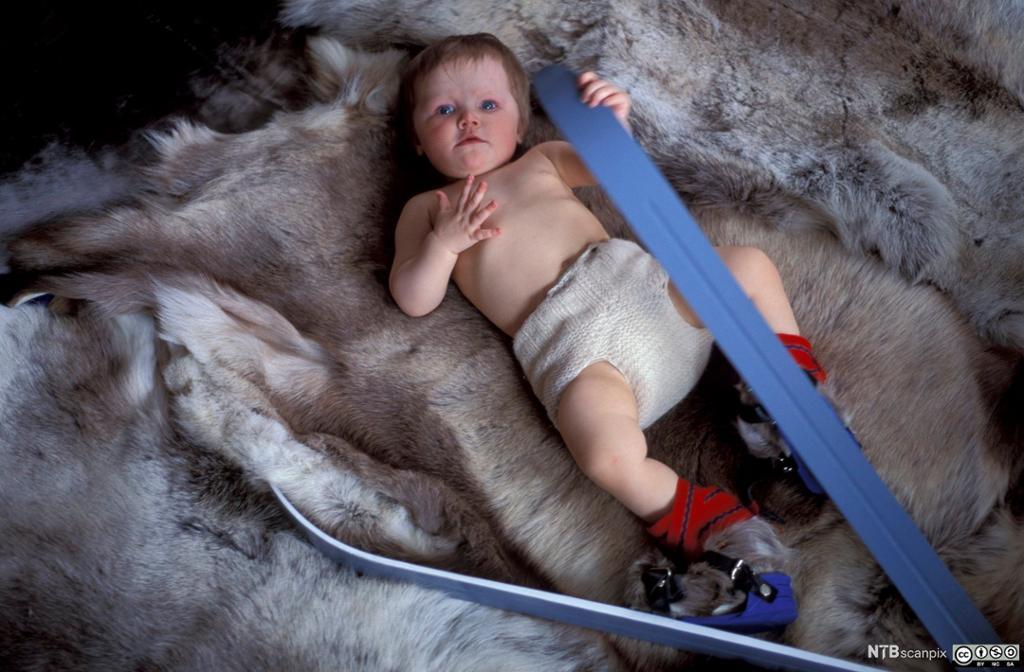 Baby med ski på beina. Foto.