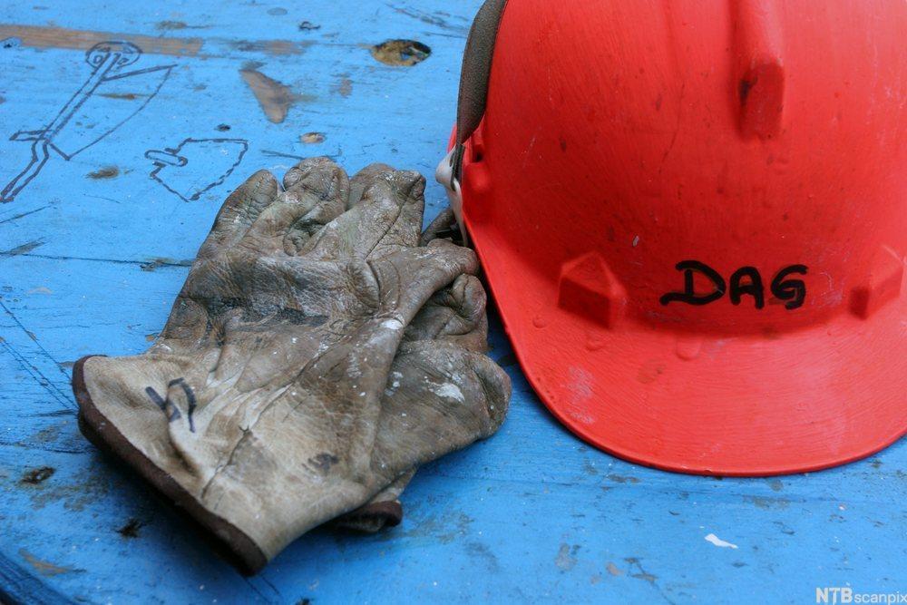 Arbeidshanske og en rød arbeidshjelm. Foto.