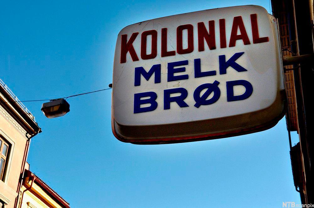 Butikkskilt med tekst. Kolonial, brød og melk. Foto.