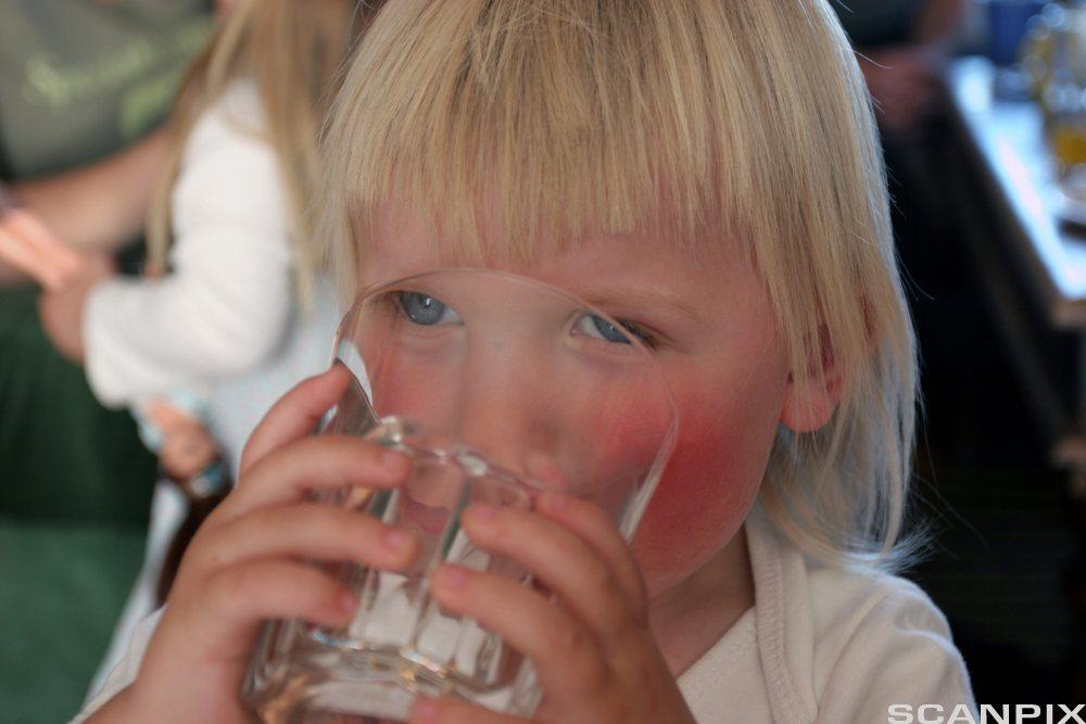 Liten gutt drikker fra vannglass. Foto.