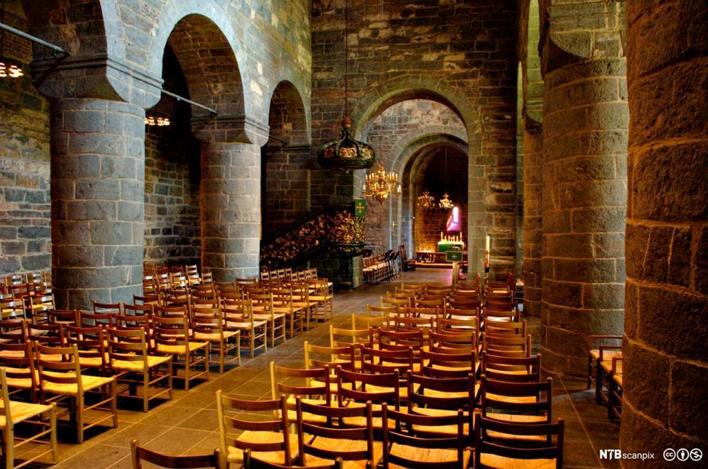 Interiør fra gammel steinkirke. Grå vegger og bueganger. Enkle pinnestoler er satt opp på rekke. Foto.
