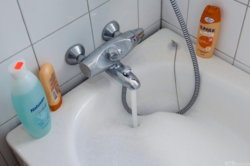 Badekar som fylles med vann som skummer. Foto.