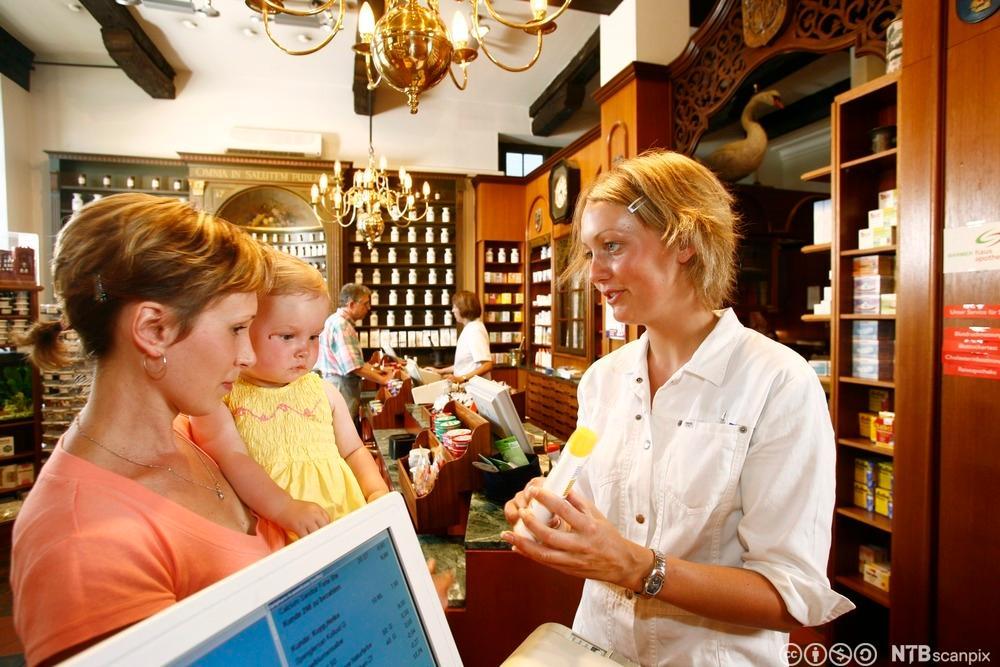 Ung kvinne selger apotekvarer. Foto.