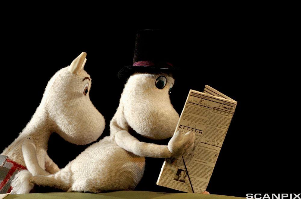 To mumier, den lene har en hatt og leser i en avisa. Foto.