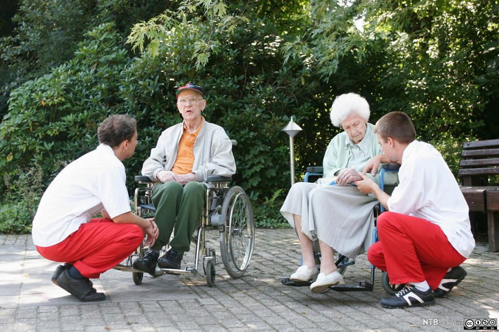 To eldre ute i rullestol kommuniserer med to helsefagarbeidere. Foto.