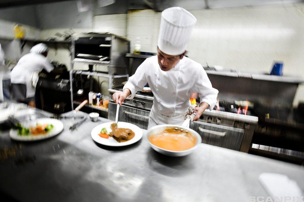 Kokk på restaurantkjøkken. Foto