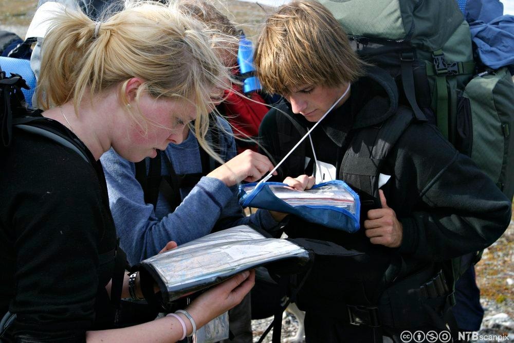 Ungdommer med kart og kompass. Foto.