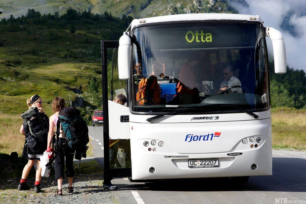Buss med passasjerer utenfor. foto.