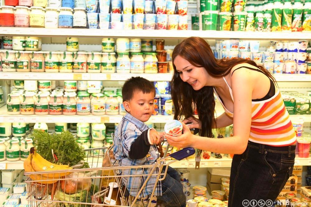Ung mor handler sunn mat i en matforetning. Foto