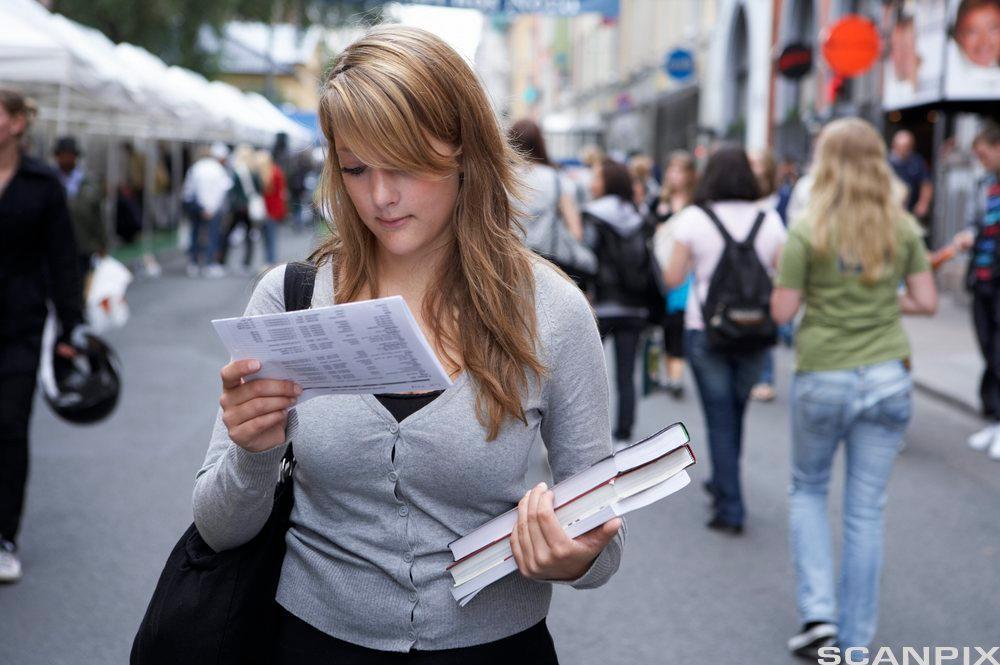 jente med papirer i hånda på gata. Foto.