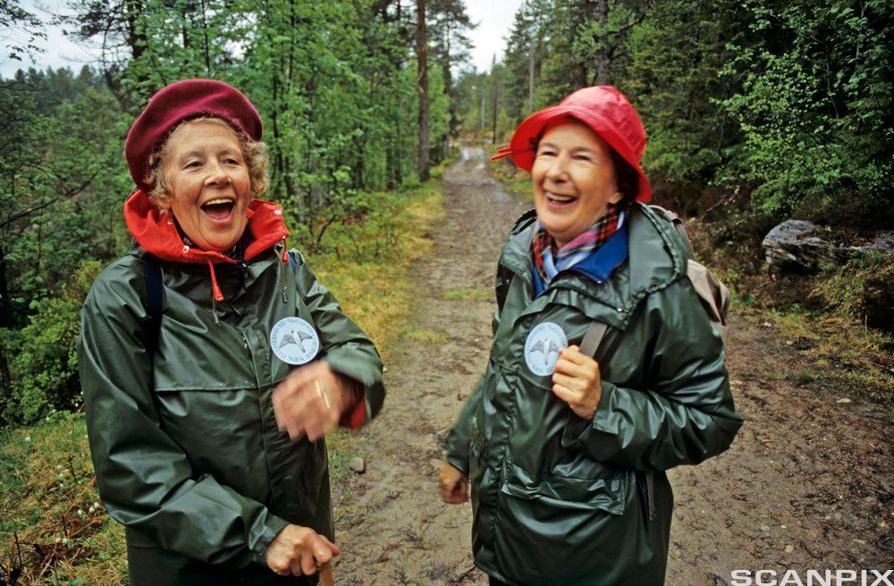 To eldre damer med regnfrakk og sydvest, de er i godt humør. Foto