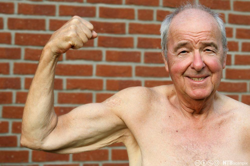 Gammel mann viser muskler. Foto.