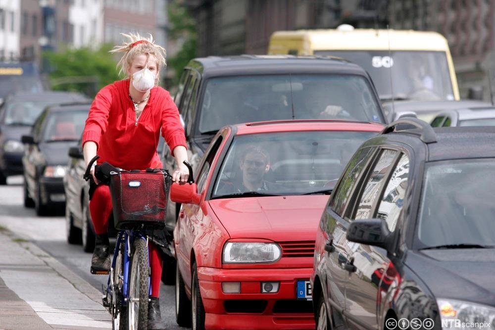 Ung kvinne med maske sykler blant biler. Foto